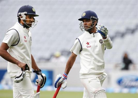 Ajinkya Rahane (R) and Rohit Sharma (L) chat as they leave the field due to bad light on day two of the first international test cricket match against New Zealand, at Eden Park in Auckland February 7, 2014. REUTERS/Nigel Marple