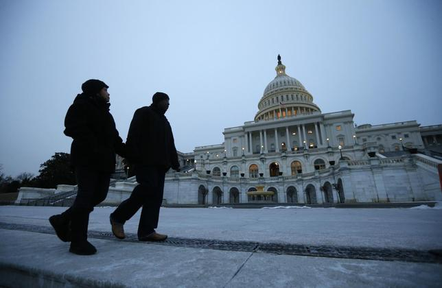 Pedestrians walk past the U.S. Capitol building prior to U.S. President Barack Obama's State of the Union address in front of the U.S. Congress, on Capitol Hill in Washington January 28, 2014. REUTERS/Kevin Lamarque