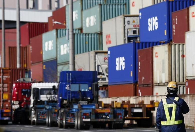 A worker stands in a container area at a port in Tokyo January 27, 2014. REUTERS/Toru Hanai