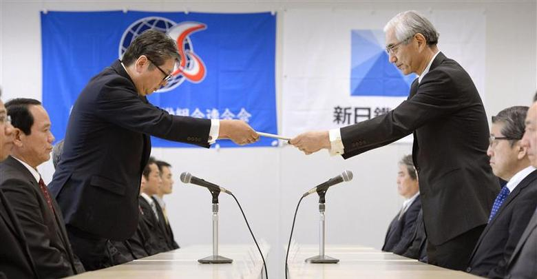 Nippon Steel & Sumitomo Metal labor union chairman Tadayuki Omori (L) submits wage hike request to the company's vice president Takao Shindo in Tokyo in this photo taken by Kyodo February 7, 2014. REUTERS/Kyodo