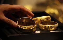 Консультант ювелирного магазина показывает посетителю золотые браслеты в Гонконге 24 апреля 2013 года. Цены на золото растут за счет возвращения на рынок китайских покупателей, но трейдеры избегают крупных ставок в ожидании отчета о занятости в США. REUTERS/Bobby Yip