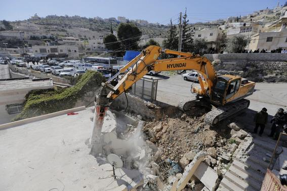A bulldozer demolishes a house in Jabel Mukaber, a Palestinian village in the suburbs of East Jerusalem, in this February 5, 2014 file picture. REUTERS-Ammar Awad-Files