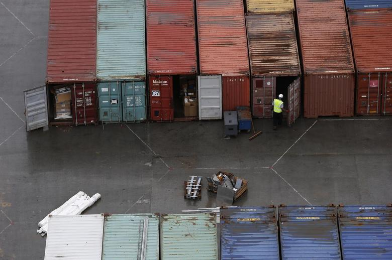 A worker opens the door of a container at DP World London Gateway container port in Essex, southern England July 30, 2013. REUTERS/Suzanne Plunkett