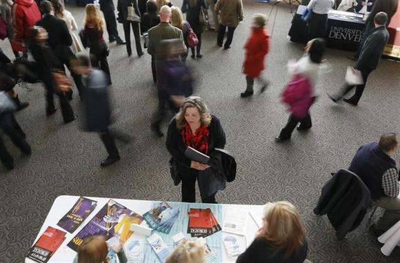 A job seeker (C) talks to an exhibitor at the Colorado Hospital Association health care career fair in Denver April 9, 2013. REUTERS/Rick Wilking/Files