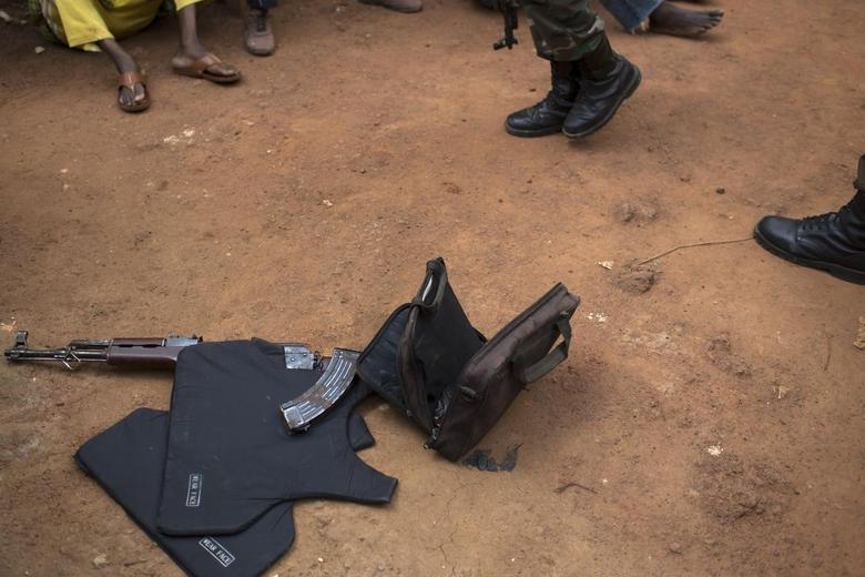 An AK-47 assault rifle with a magazine of ammunition, a bag of grenades and a flak jacket are seen on the ground after African Union (AU) peacekeepers found them during a search and disarmament operation in Kilometre 9 (PK9) in the capital Bangui February 7, 2014. REUTERS/Siegfried Modola