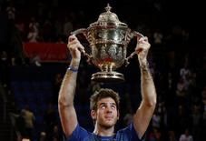 Juan Martin Del Potro of Argentina raises the winner's trophy after he won his final match against Switzerland's Roger Federer at the Swiss Indoors ATP tennis tournament in Basel October 27, 2013. REUTERS/Arnd Wiegmann