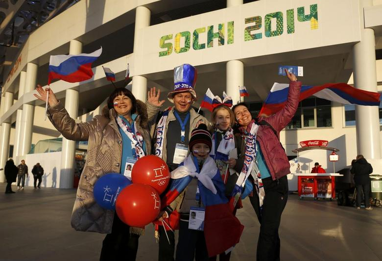 People wave as they arrive for the opening ceremony of the 2014 Sochi Winter Olympics, February 7, 2014. REUTERS/Mark Blinch