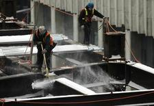 A construction worker sweeps snow from iron beams on the Bay Adelaide East office building site after a storm in Toronto February 6, 2014. REUTERS/Chris Helgren