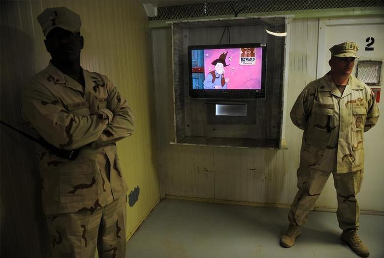 Guards stand next to a television showing a cartoon as journalists visit the movie room at the Camp Four detention facility at the U.S. Naval Station Guantanamo Bay December 10, 2008. REUTERS/Mandel Ngan/Pool
