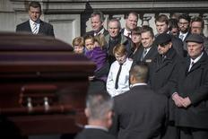 Mimi O'Donell, pareja del actor Phillip Seymour Hoffman, carga a su hija Willa (vestida de púrpura) al lado de su hijo Cooper mientras el ataúd con los restos del actor llegan para su funeral en Manhattan, en Nueva York, 7 de febrero del 2014. La familia y los amigos cercanos dieron su último adiós el viernes en un funeral privado al actor, cuya trágica muerte a los 46 años, a causa aparentemente de una sobredosis, ha robado al mundo del entretenimiento uno de sus mejores talentos. REUTERS/Brendan McDermid