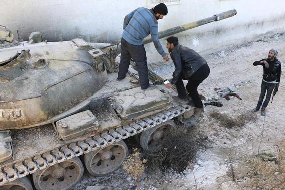 Rebel fighters stand on a tank belonging to the Islamic Front near Nairab military airport, which is controlled by forces loyal to Syria's President Bashar al-Assad, in Aleppo February 7, 2014. REUTERS-Hosam Katan