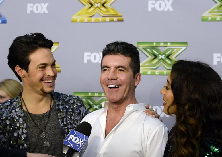 Alex Kinsey (L) and Sierra Deaton (R) look at their mentor and judge Simon Cowell (C) as he speaks during an interview backstage after the folk duo won ''The X Factor '' in Los Angeles, California, December 19, 2013. REUTERS/Kevork Djansezian