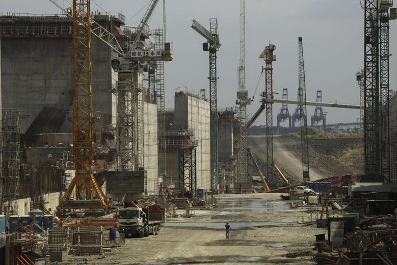 A man walks between cranes during a tour organized by the Panama Canal authorities of the Panama Canal Expansion project construction site on the Pacific side in Panama City February 5, 2014. REUTERS/Carlos Jasso