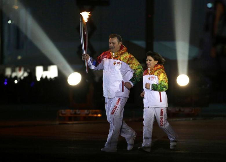 Former hockey player Vladislav Tretiak (L) and figure skater Irina Rodnina run to light the Olympic Cauldron during the opening ceremony of the 2014 Sochi Winter Olympics, February 7, 2014. REUTERS/Matt Slocum/Pool