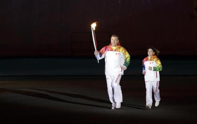 Former hockey player Vladislav Tretiak (L) and figure skater Irina Rodnina run to light the Olympic cauldron during the opening ceremony of the 2014 Winter Olympics in Sochi February 7, 2014. REUTERS/Matt Slocum/Pool