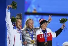 Gold medalist Sage Kotsenburg of the U.S., silver medalist Staale Sandbech (L) of Norway and bronze medalist Mark McMorris (R) of Canada wave during the medal ceremony for the men's snowboard slopestyle competition in the Olympic Plaza at the 2014 Sochi Olympic Games February 8, 2014. REUTERS/Shamil Zhumatov