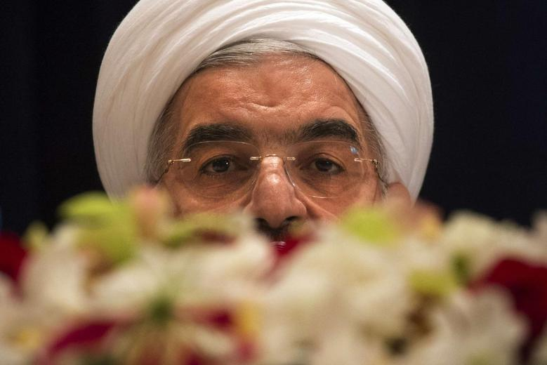 Iran's President Hassan Rouhani takes questions from journalists past a bouquet of flowers at a news conference in New York September 27, 2013. REUTERS/Adrees Latif