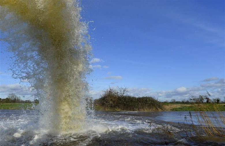 An emergency flood pump ejects water into the River Parrett near the village of Moorland in south west England February 7, 2014. REUTERS/Toby Melville