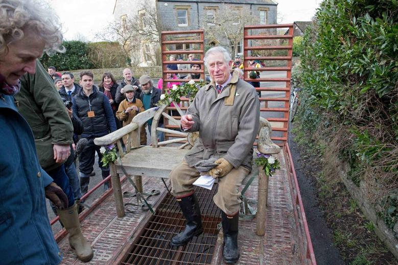 Britain's Prince Charles sits on a decorated garden bench as he travels in a trailer through flood water in Muchelney, on route to Thorney Moor Farm February 4, 2014. REUTERS/Jack Hill/The Times/Pool