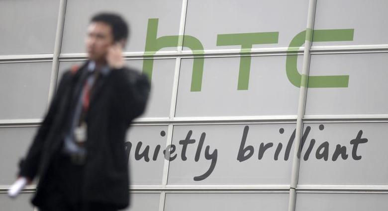 Visitors walk past a HTC sign at the GSMA Mobile World Congress in Barcelona, February 14, 2011. REUTERS/Albert Gea