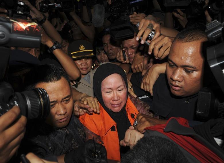 Banten governor Ratu Atut Chosiyah (C), wearing an KPK orange vest, walks as she is detained at the national anti-graft agency (KPK) office in Jakarta December 20, 2013. REUTERS/Stringer