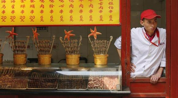 A food vendor waits for customers at a shopping district in Beijing May 6, 2013. REUTERS/Kim Kyung-Hoon/Files