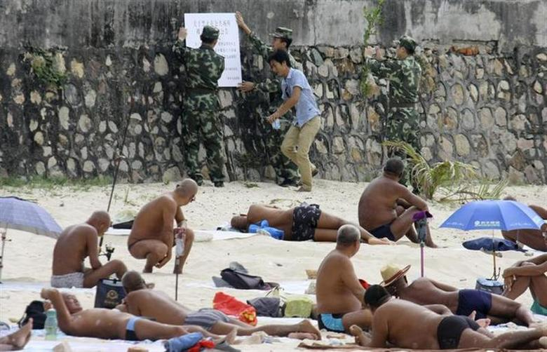 Sunbathers look as government officials put up a notice on banning nudity in public areas, at a beach in Sanya, Hainan province February 8, 2014. REUTERS/Stringer