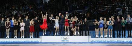 Российская сборная по фигурному катанию (в центре) радуется победе в командных соревнованиях на Олимпиаде в Сочи 9 февраля 2014 года. Второй день зимних Олимпийских игр, открывшихся в Сочи в пятницу, принес российской сборной четыре медали, одна из которых - в фигурном катании - золотая. REUTERS/Alexander Demianchuk