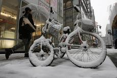 Женщина проходит мимо заснеженного велосипеды в токийском районе Гиндза 8 февраля 2014 года. Одиннадцать человек погибли, более тысячи получили ранения и десятки тысяч людей остались без электричества в результате мощнейшей за последние несколько десятков лет снежной бури, обрушившейся на Токио и районы вокруг японской столицы. REUTERS/Toru Hanai