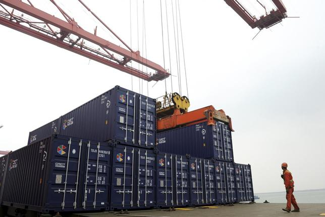 A worker stands near a crane unloading shipping containers from a cargo ship at a port in Lianyungang, Jiangsu province November 8, 2013. REUTERS/China Daily
