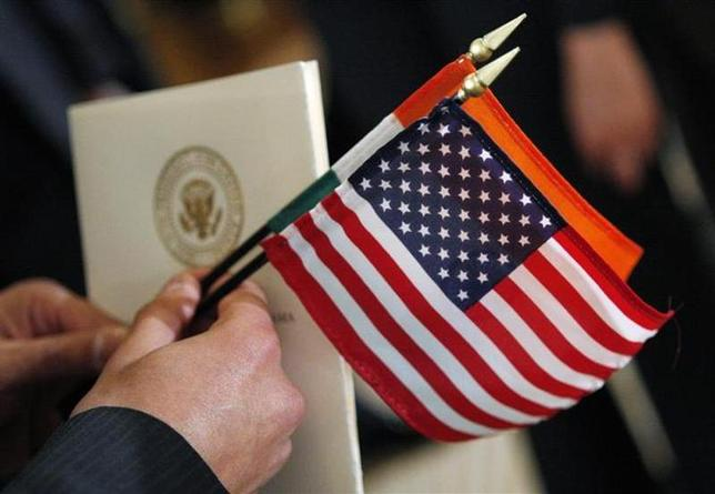 A guest holds the flags of the United States and India and a program as U.S. President Barack Obama welcomes Indian Prime Minister Manmohan Singh at an official arrival ceremony in the East Room at the White House in Washington, November 24, 2009. REUTERS/Jim Young/Files