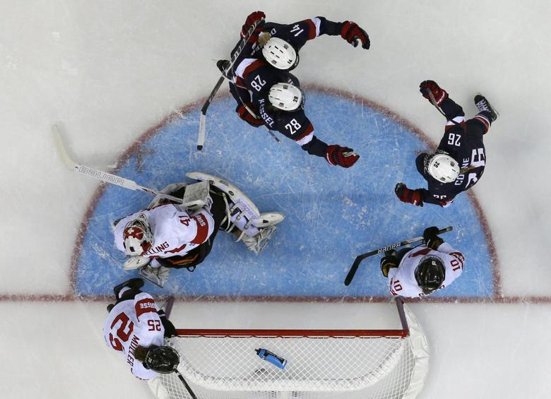 Team USA's Kendall Coyne (26) celebrates her goal with teammates Amanda Kessel (28) and Brianna Decker as Switzerland's goalie Florence Schelling (41) with teammates Alina Muller (25) and Nicole Bullo react during the third period of their women's preliminary round hockey game at the Sochi 2014 Winter Olympic Games February 10, 2014. REUTERS/Mark Blinch