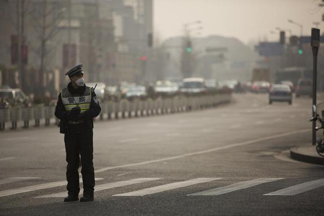 A policeman wearing a face mask stands on a road during a hazy day in Shanghai, January 20, 2014. REUTERS/Aly Song