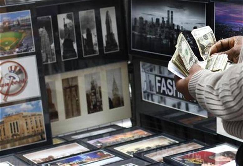 A vendor counts money at his photograph stand at Times Square in New York October 14, 2010. REUTERS/Shannon Stapleton/Files