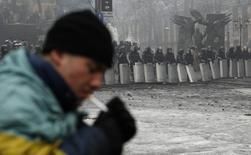 Антиправительственный демонстрант курит на баррикадах в Киеве 10 февраля 2014. Евросоюз должен быть готовым наложить санкции на Украину, если её власти будут упорствовать в применении силы к протестующим, сказал глава МИД Чехии, призвав сопротивляться возвращению авторитаризма советского толка. REUTERS/David Mdzinarishvili