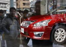 Nissan Motor's Teana sedan is displayed as pedestrians are reflected in a window at the company's showroom in Tokyo February 10, 2014. REUTERS/Toru Hanai
