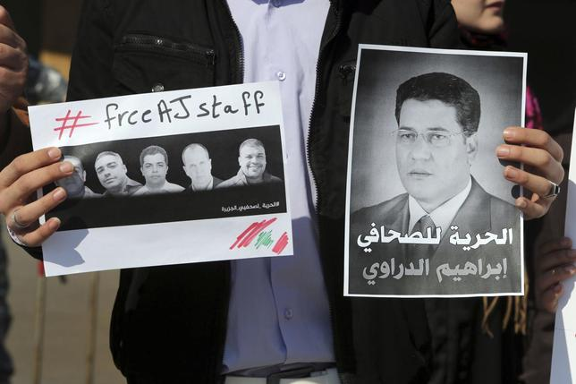 A protester holds signs during a protest against the detainment of Al Jazeera journalists in Egypt, in downtown Beirut February 8, 2014. REUTERS/Hasan Shaaban