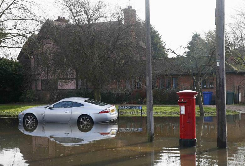 UK's Cameron visits flooded areas as blame game...