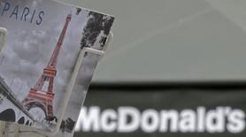 A postcard showing the Paris city landmark, the Eiffel Tower, is seen in front of a McDonald's fast-food restaurant in Paris, January 22, 2014. REUTERS/Christian Hartmann