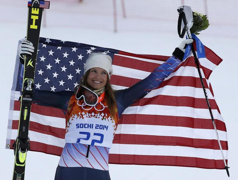 Third-placed Julia Mancuso of the U.S. celebrates with a U.S. flag during the flower ceremony after the women's alpine skiing super combined event during the 2014 Sochi Winter Olympics at the Rosa Khutor Alpine Center February 10, 2014. REUTERS/Leonhard Foeger
