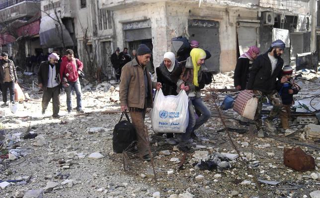 Civilians carry their belongings as they walk towards a meeting point to be evacuated from a besieged area of Homs February 7, 2014. REUTERS/Yazan Homsy