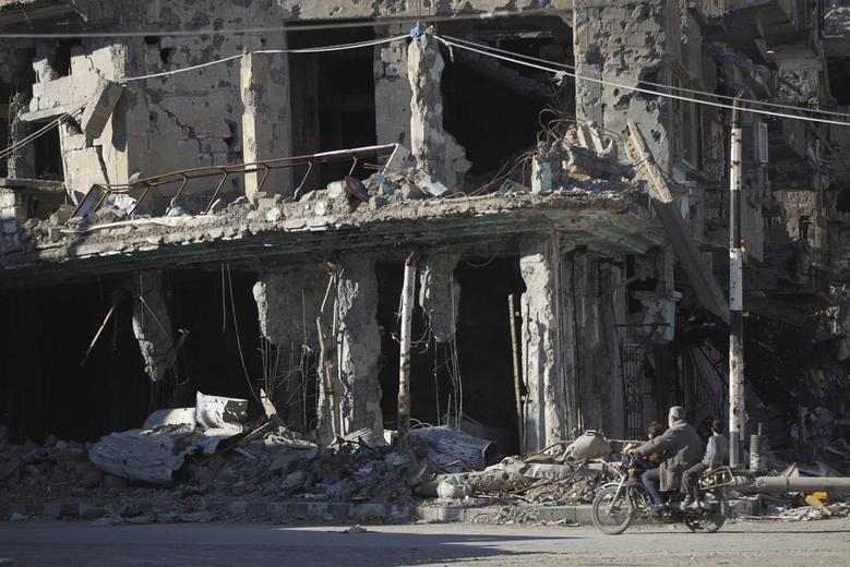 Residents ride a motorcycle along a damaged street in Deir al-Zor, eastern Syria February 9, 2014. REUTERS/Khalil Ashawi