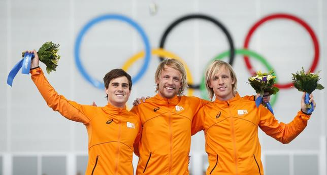 Winner of the men's 500 meters speed skating competition Michel Mulder of the Netherlands (C), second placed Jan Smeekens of the Netherlands (L) and third placed Ronald Mulder of the Netherlands celebrate at the flower ceremony for the event at the 2014 Sochi Winter Olympics, February 10, 2014. REUTERS/Marko Djurica