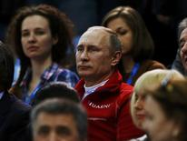 Russian President Vladimir Putin watches from the stands during the Team Ladies Free Skating Program at the Sochi 2014 Winter Olympics, February 9, 2014. REUTERS/Alexander Demianchuk