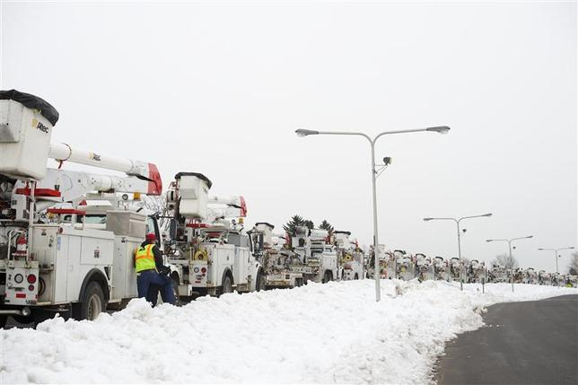 Numerous electric line crew trucks contracted from Georgia are parked in a line outside William Tennent High School in Warminster, Pennsylvania, February 8, 2014, in the aftermath of an ice storm which hit the Philadelphia area, where an estimated 280,000 PECO customers from the region lacked power. REUTERS/Mark Makela