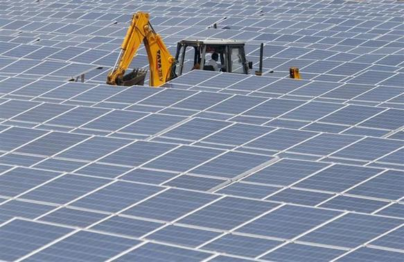 An excavator works among photovoltaic solar panels at the Gujarat solar park under construction in Charanka village in Patan district of Gujarat April 14, 2012. REUTERS/Amit Dave/Files