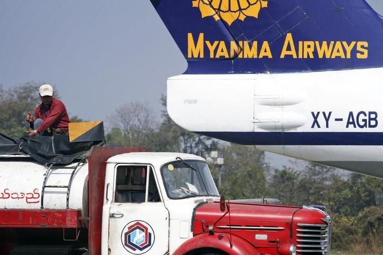 A man prepares to fuel an ageing Myanma Airways airplane in the city of Myitkyina in northern Myanmar February 27, 2012. REUTERS/Staff