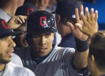Cleveland Indians' Michael Brantley (C) is congratulated by teammates in the dugout after he scored in the eighth inning of their MLB baseball game against the Toronto Blue Jays in Toronto April 3, 2013. REUTERS/Fred Thornhill