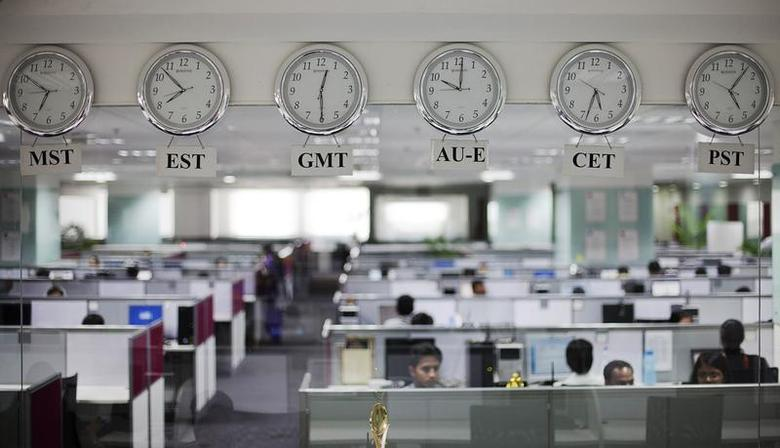 Workers are pictured beneath clocks displaying time zones in various parts of the world at an outsourcing centre in Bangalore February 29, 2012. REUTERS/Vivek Prakash/Files