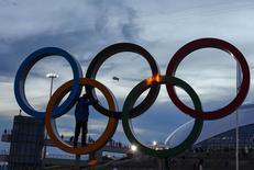 Болельщик стоит в олимпийских кольцах в Сочи 9 февраля 2014 года. о вторник на зимних Олимпийских играх в Сочи будут разыграны восемь комплектов медалей. REUTERS/Shamil Zhumatov